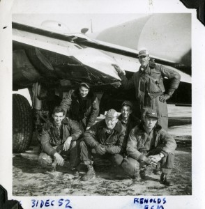 John Greening (center front)--seen in his yet-unpainted cap--poses with his crew in front of their B-29 in Okinawa. Photograph dated December 31, 1952.