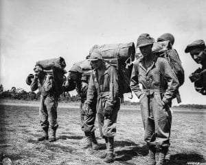 "Soldiers with the 14th Portable Hospital Unit, part of the 32nd ""Red Arrow"" Division's 3rd Battalion, 127th Infantry regiment, move out along the Dubadura air strip eight miles south of Buna, Papua New Guinea after disembarking a troop transport plane Dec. 15, 1942. U.S. Army Signal Corps photo"