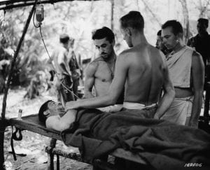 "Cpl. Clayton Mitchell and Maj. William Carlick administer blood plasma to a wounded 32nd ""Red Arrow"" Soldier at 3rd Portable Hospital near Buna Village Jan. 1, 1943. U.S. Army Signal Corps photo"