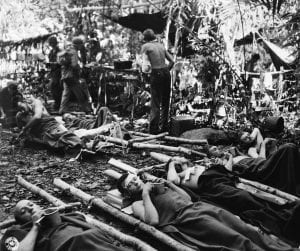 "Wounded men at the 32nd ""Red Arrow"" Division's 4th Portable Hospital near Buna Village, New Guinea, wait to be evacuated to Dobodura Dec. 31, 1942. U.S. Army Signal Corps photo"