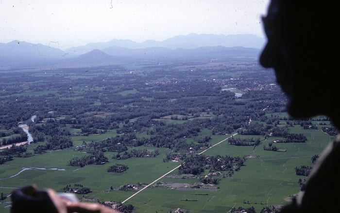 Vietnam countryside seen from a helicopter, soldier's silhouette in the foreground